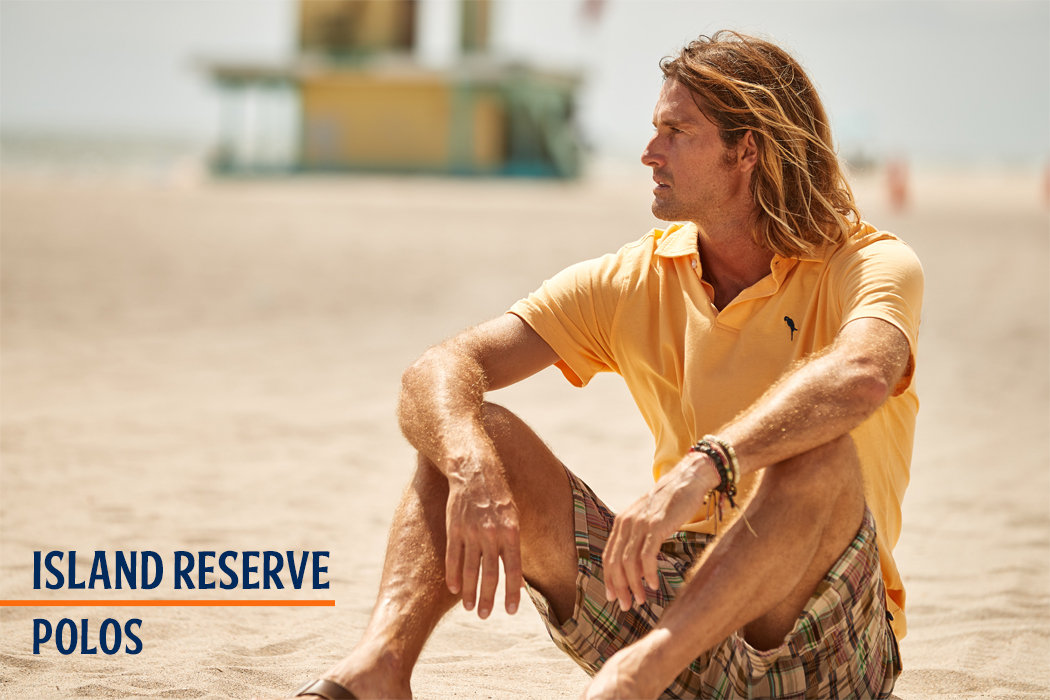 Man sitting on a beach wearing a yellow island reserve polo shirt and checkered shorts